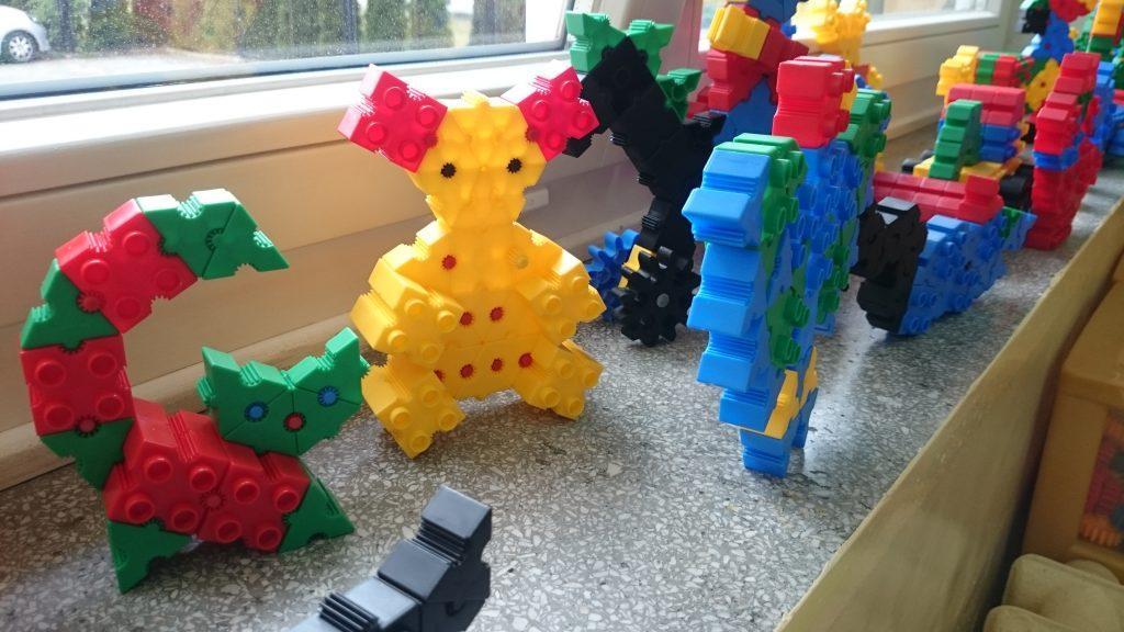 Zdjęcie zachęca do odwiedzenia galerii - Przestrzeń. Na zdjęciu są zabawki złożone z klocków.