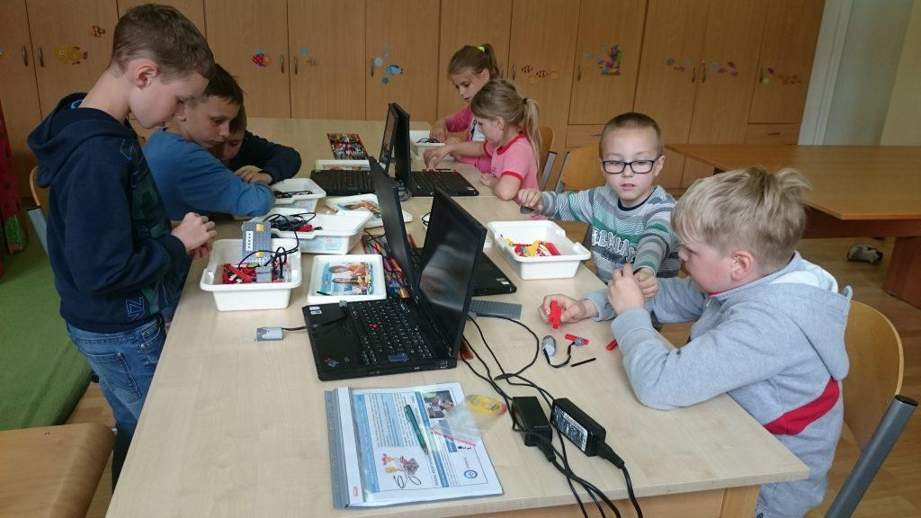 Odnośnik do Galerii Robotyka. Na zdjęciu dzieci budują roboty z zestawów.