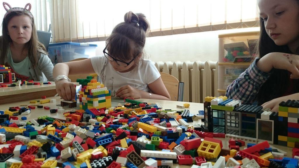 Zdjęcie z odnośnikiem do Galerii - Akademia Budowania Klockami Lego. Dziewczynka układająca klocki